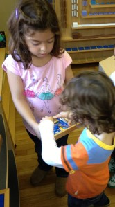 girl helps younger student by getting him some materials to work with and providing basic instructions