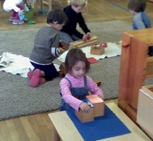 children work independently and in groups in the smoothly functioning primary Montessori classroom