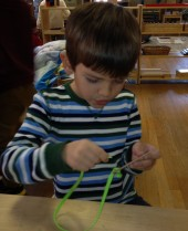 boy works diligently at lacing a card