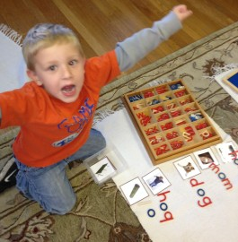 boy shows excitement and pride for his work with the moveable alphabet