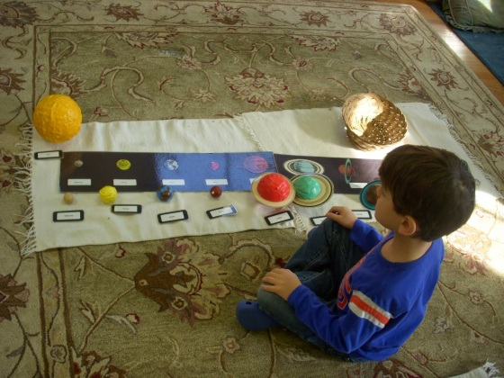This K student learns astronomy Montessori style---all senses are engaged.