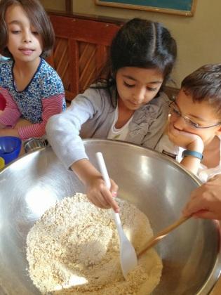 Elementary students prepare dough for las arepas, Venezuelan tortillas.