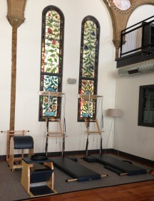 Handmade pilates equipment lines walls graced with stained glass