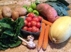 From left: a very sturdy head of deep green lettuce, potatoes, green peppers, a gargantuan sweet potato, lacinato kale, spaghetti squash, pop corn, cherry tomatoes, and garlic