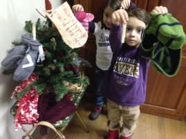 These students use clothespins to attach hats and matching mittens to the primary classes' Mitten Tree. (The Ravens did win that day, surely due in part to this show of spirit among the little ones.)