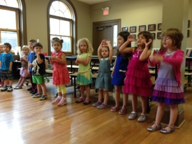 Primary students practice recognizing the notes of the music scale and demonstrating them with hand gestures.
