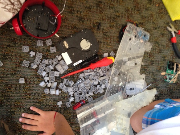 Various parts from a disassembled alarm clock and a disassembled keyboard will find new life as components of a pinbug machine!
