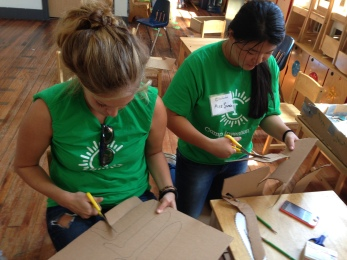 Camp Instructors Miss Katie (left) and Miss Sarah (right) help the 1st-grade campers with some of the more arduous cardboard cutting, but constructing the pinbug machines will be all done by the campers themselves.